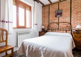 Dormitorio de matrimonio con frontal de ladrillo
