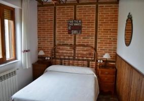 Dormitorio de matrimonio con pared de ladrillo