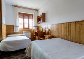 Dormitorio doble con colchas de color blanco y friso de madera
