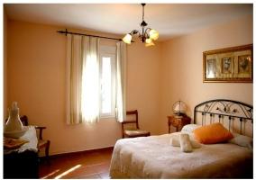 Habitación con cama de matrimonio y cabecero en forja