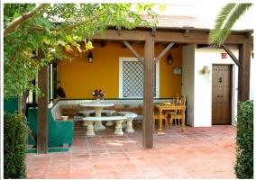 Rincón techado con mesa y bancos de piedra