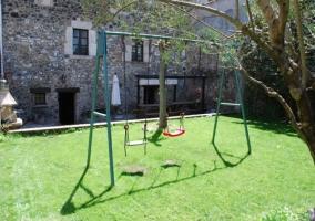 Jardín con césped y columpios en casa rural