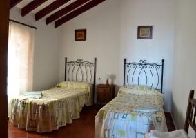 Dormitorio doble con techo y vigas tipo abuhardillado