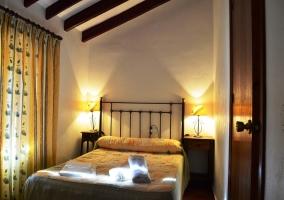 Dormitorio cama de matrimonio con cabecero de hierro techo abuhardillado con vigas de madera