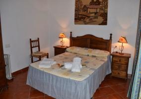 Dormitorio principal con suelo de barro y cabecero de madera