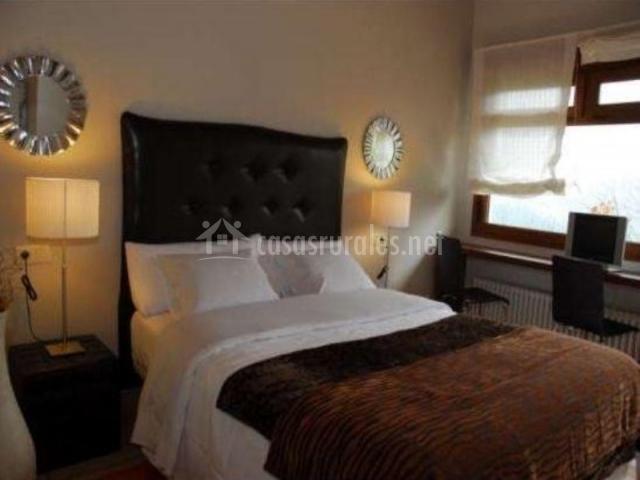 Dormitorio con cama doble y cabecero negro