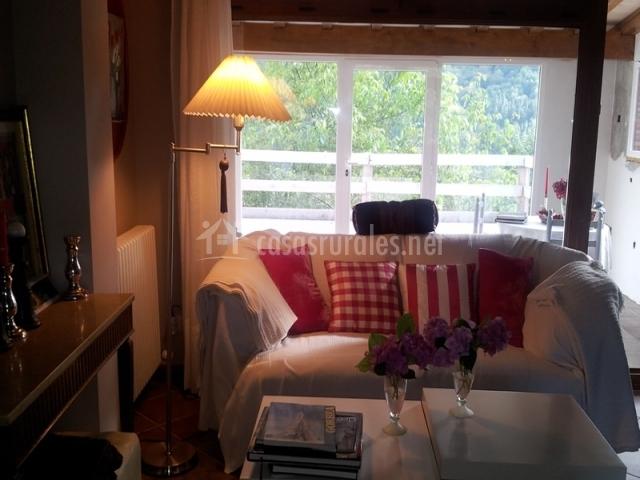 Salón con sillón blanco y mesas
