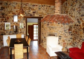 Sala de estar con butacas y cartel en la pared de la casa rural