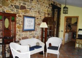 Rincón del salón con paredes de piedra de la casa rural