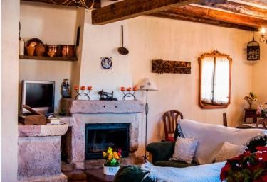 Salón con chimenea de piedra y mobiliario