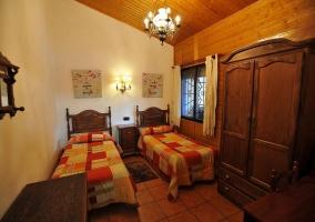 Dormitorio doble con camas individuales y colchas naranjas