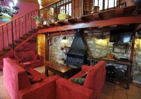 Salón en tonos rojos con chimenea y techos altos