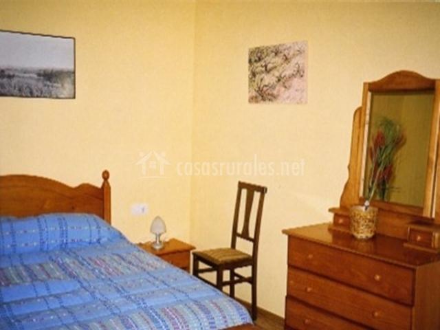 Habitación de matrimonio con una gran cómoda y un espejo