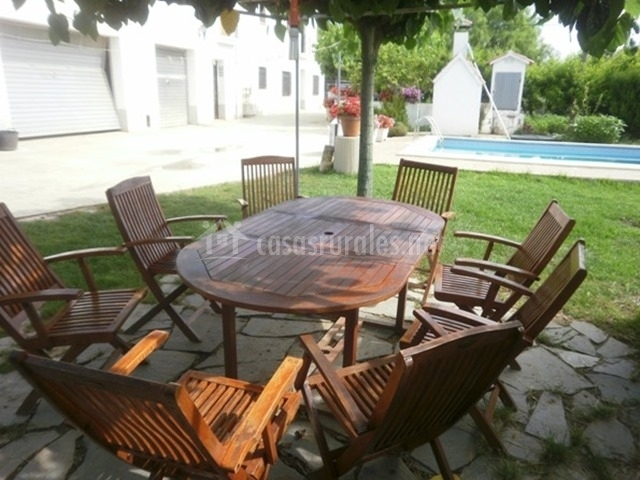 Mesa con sillas de madera en el jardín de la vivienda