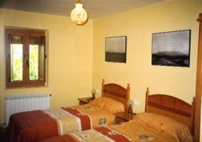 Habitación doble con camas individuales con cuadros en las paredes