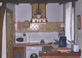 Cocina americana con barra de ladrillo y electrodomésticos blancos