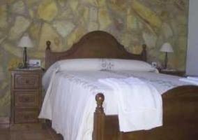 Habitación con cama de matrimonio y colcha blanca
