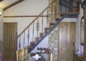 Zona de comedor con escaleras de piedra que suben a la buhardilla