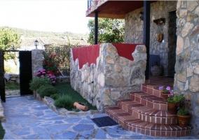 Vistas de la zona exterior con piscina y terraza cubierta con barbacoa en la casa rural
