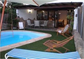 Vistas de la piscina y la terraza cubierta de la casa rural
