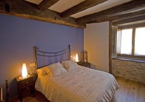 Dormitorio con cama de matrimonio y cabecero de hierro