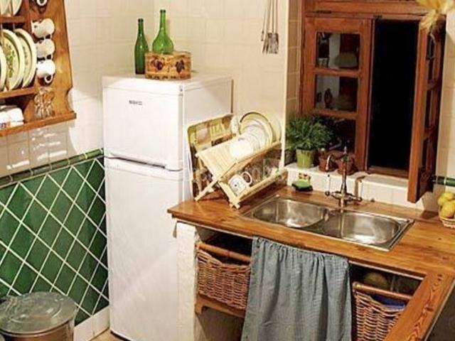 Cocina con azulejos en color verde y nevera