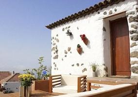 Acceso principal a la casa con fachada en blanco y piedra