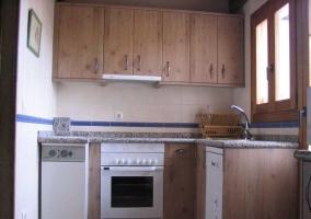 Mesa de comedor de madera y rectangular con planta colgada en la pared