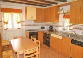 Cocina con muebles de madera y mesa de comedor de casa rural