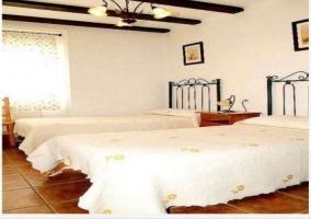 Habitación con 2 camas y cabeceros de metal.