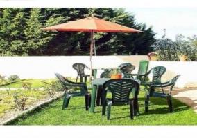 Jardín con mesa, sillas y sombrilla