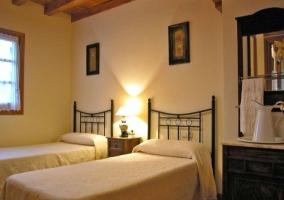 Dormitorio con camas individuales y cabeceros de hierro