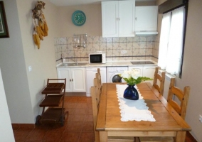 Cocina con mesa de madera y su conjunto de sillas junto a la ventana