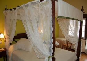 Dormitorio de matrimonio con dosel de madera y telas
