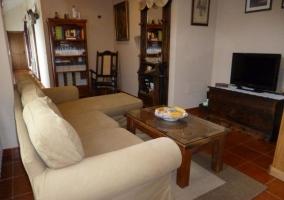 Sala de estar con mesa auxiliar de madera y centro de flores