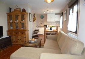 Sala de estar con sillones en crema y cocina comedor al fondo