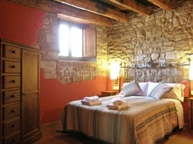Dormitorio doble con pared parcialmente en piedra