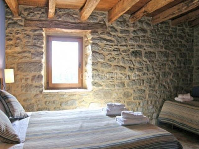 Dormitorio triple con techos de madera