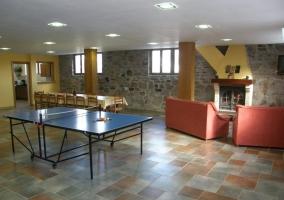 Sala de juegos con sofás y ping-pong y mesa de comedor
