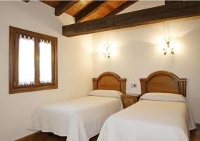 Habitación doble con camas en blanco y muebles de madera