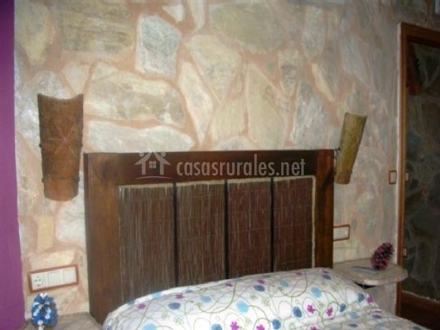 Dormitorio con colcha de flores de colores y pared de piedra con cabecero étcnico