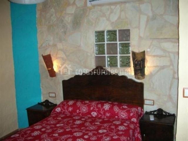 Dormitorio con colcha roja de flores blancas y pared de piedra