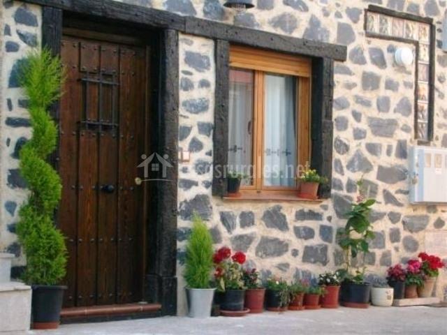 Fachada de piedra blanca y negra y maceteros en la puerta