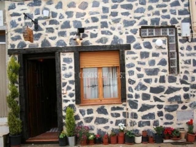 Fachada exterior de la casa en piedra blanca y negra