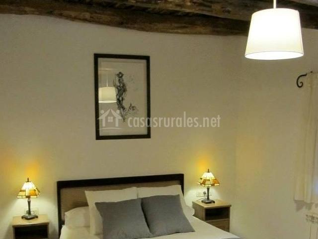 Dormitorio de matrimonio con cojines grises y vigas de madera