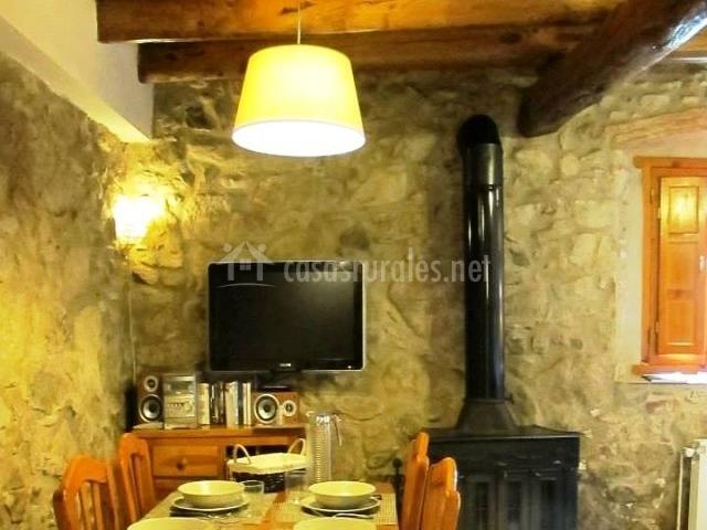 Mesa del comedor con estufa y paredes de piedra