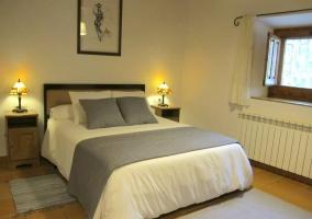 Dormitorio de matrimonio con cojines grises