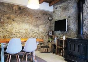 Sala de estar con paredes de piedra y mobiliario