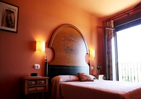 Dormitorio con cama de matrimonio y cabecero en madera