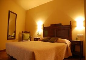 Dormitorio doble de la casa rural con cabecero de madera